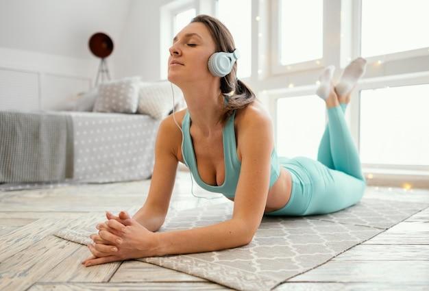 マットの上で運動し、音楽を聴く女性