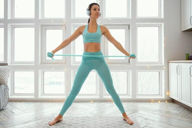 Женщина тренируется на коврике с резинкой