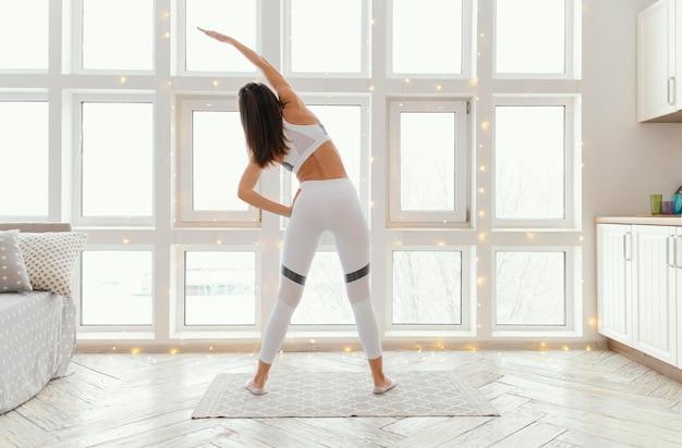 Женщина, тренирующаяся на коврике