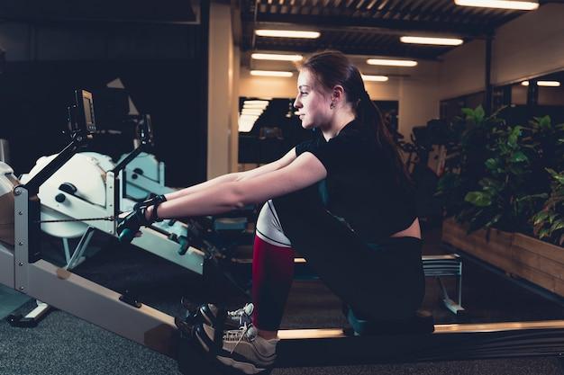 ジム、ローイングマシンで運動する女性