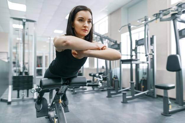 현대 스포츠 체육관에서 기계에 운동하는 여자