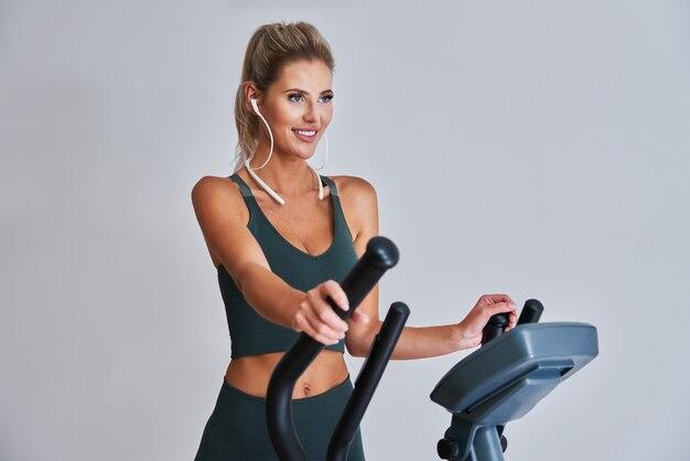 Женщина, тренирующаяся на x-trainer в фитнес-студии