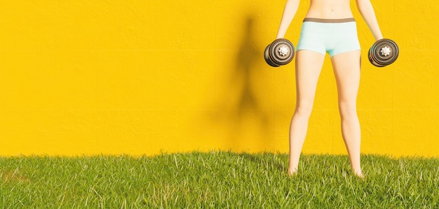 Woman exercising outdoors holding weights with yellow wall in the surface and grass on the ground
