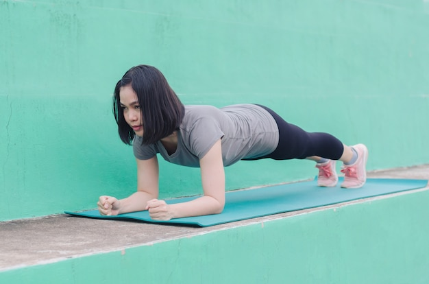 Woman exercising pose plank on a green yoga mat outdoor in stadium