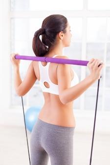 Женщина тренируется. вид сзади молодой женщины, тренирующейся в спортивном клубе