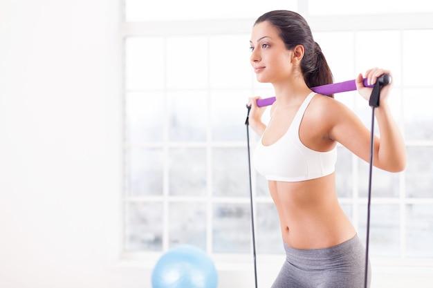 Женщина тренируется. вид сбоку уверенно молодой женщины, тренирующейся в спортивном клубе