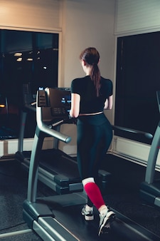 Woman exercising on treadmill in gym