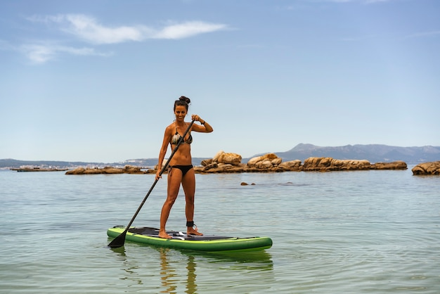 Woman exercising water sport of paddle surf in a calm sea