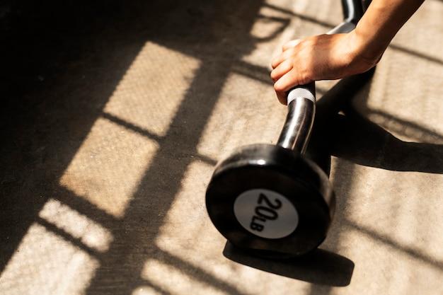 Женщина делает тяжелую атлетику со штангой в фитнес-зале