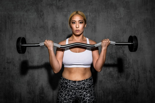 Woman exercising weighlifting with barbell at fitness gym
