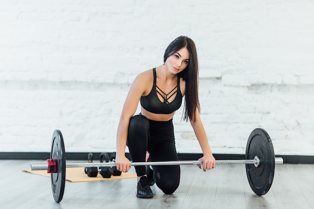 Woman exercising with barbell in fitness class of modern loft gym
