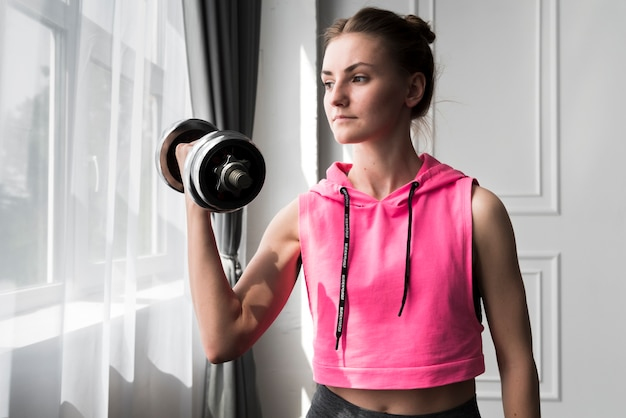 Woman exercising with dumbbell at home