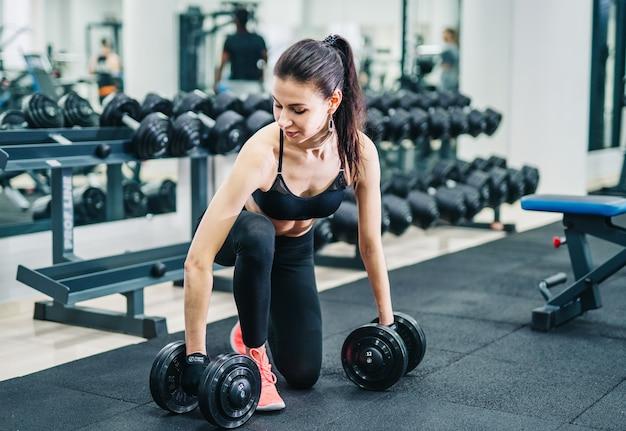 ジムでダンベルの筋肉で運動している女性。スポーツ、フィットネス、健康的なライフスタイルのコンセプト。