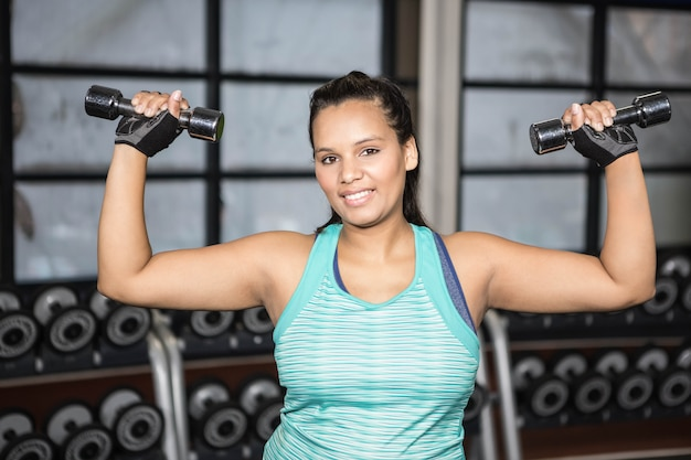 Woman exercising with dumbbells in the gym