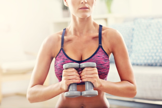 Woman exercising with dumbbells at home