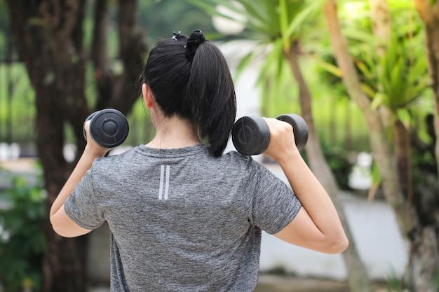 일몰, 건강 한 여자 아령 운동하는 동안 공원에서 아령으로 운동하는 여자. 아시아 여자.