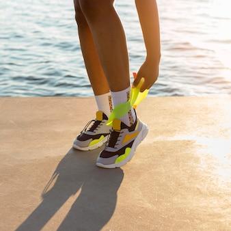 Donna che si esercita con la fascia elastica in riva al lago