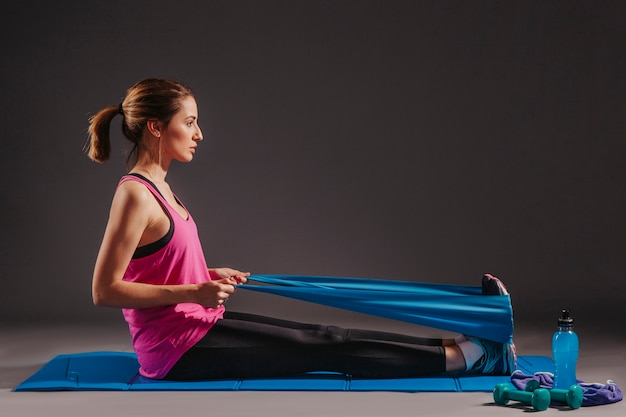 Woman exercising with elastic band on mat
