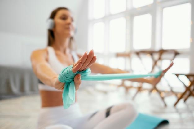 Donna che si esercita con la fascia elastica durante l'ascolto di musica