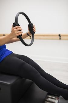 Женщина тренируется с кольцом пилатеса в тренажерном зале