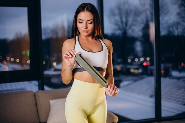 Donna che si esercita con l'elastico a casa