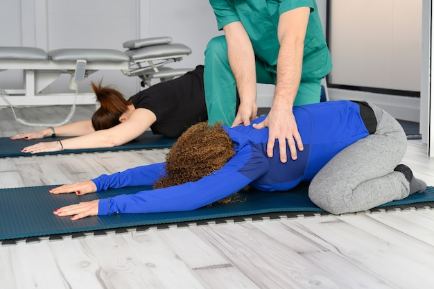 Woman exercising with therapist on yoga mat at clinic.