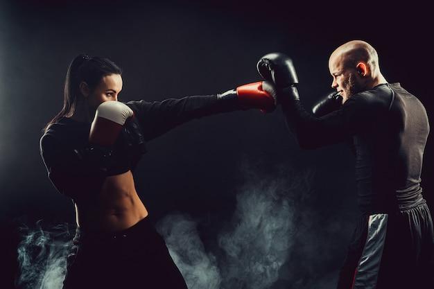 ボクシングと自己防衛のレッスンでトレーナーと運動する女性