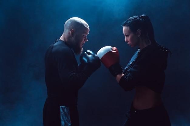 Женщина, тренирующаяся с тренером на уроке бокса и самообороны, студия, дым в космосе