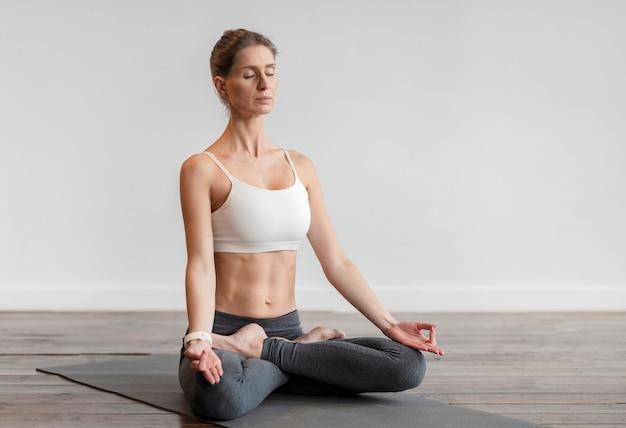 Женщина упражнениями йоги дома на коврике