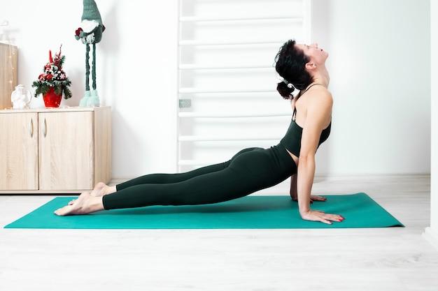 Женщина упражнениями йоги в позе собаки вверх дома