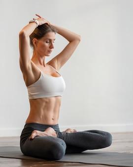 Женщина упражнениями йоги на коврике дома