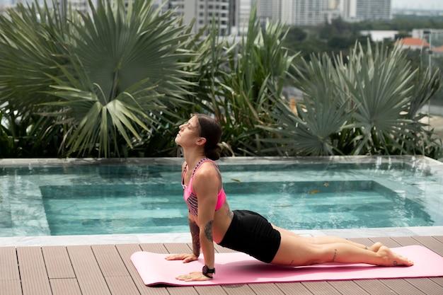 Женщина упражнения позы йоги на открытом воздухе у бассейна