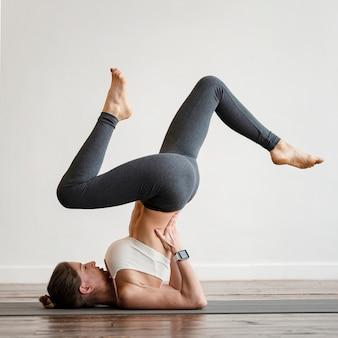Женщина упражнения позы йоги дома на коврике