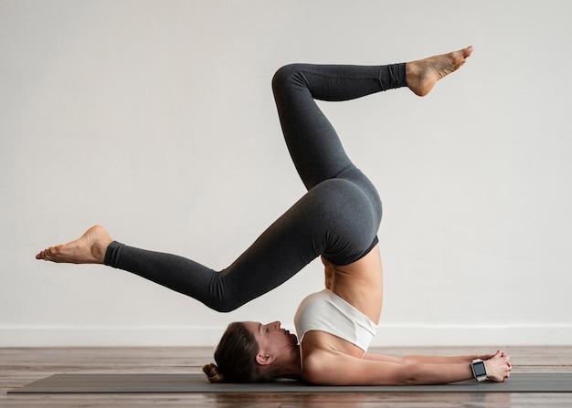 Donna che esercita posizioni yoga sulla stuoia