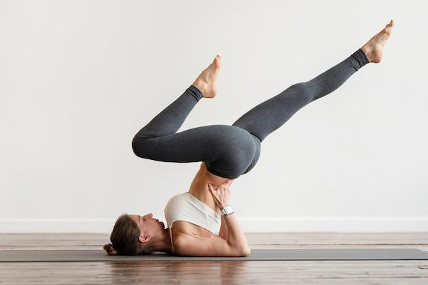 Женщина упражнения позы йоги на коврике дома