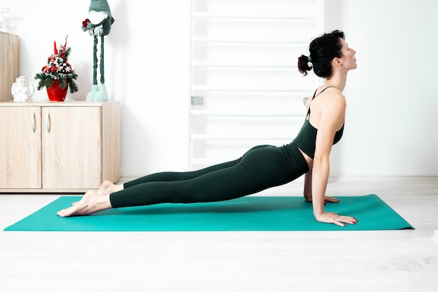 Woman exercising yoga in a upward dog position at home