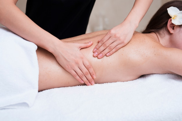 Woman exfoliating clients back at spa