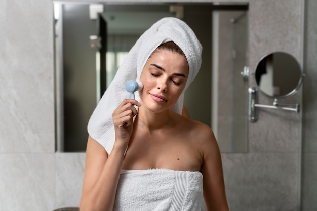 Woman exfoliating her face with a brush