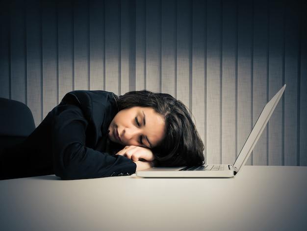 Женщина, истощенная от переутомления, спит за компьютером