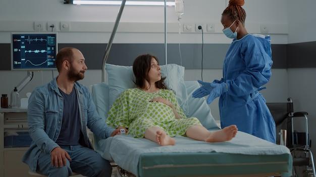 病棟に座っている子供を期待している女性
