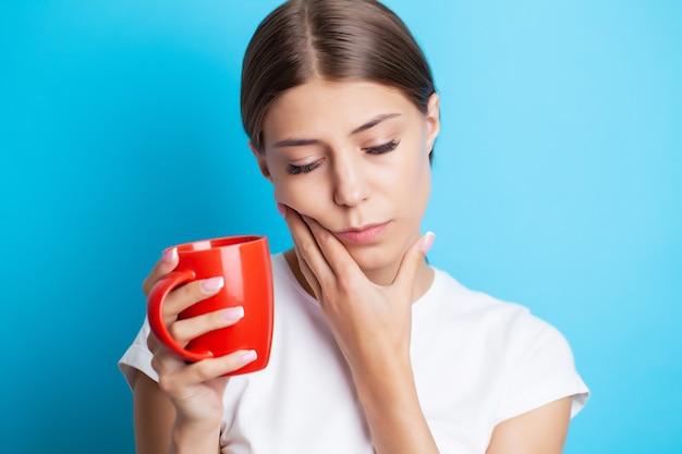 Женщина испытывает сильную зубную боль, прижав руку к щеке