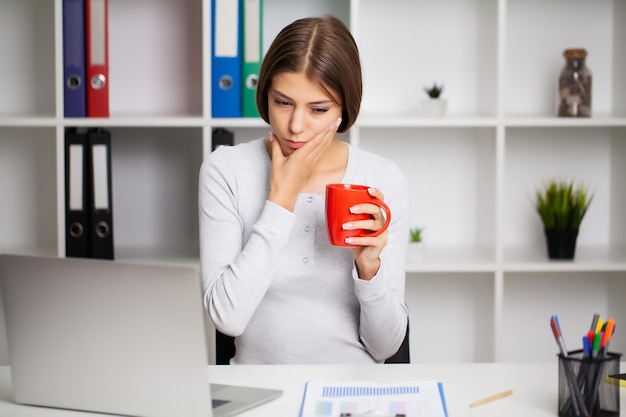 頬に手をかざす重度の歯痛を経験している女性。