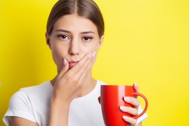 Женщина испытывает сильную зубную боль, прижимая руку к щеке.