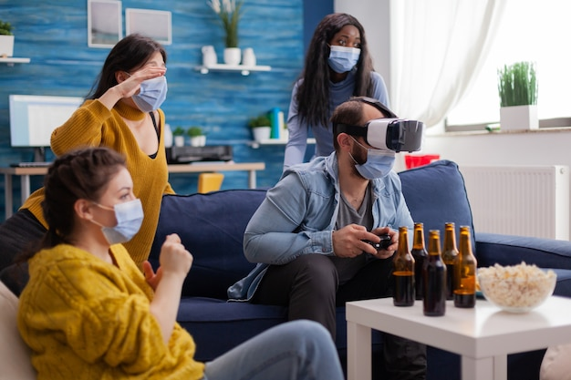 Woman experiencing virtual reality playing video games with vr headset wearing face mask while friends are cheering up keeping social distancing wearing face mask to prevent infection with virus, beer