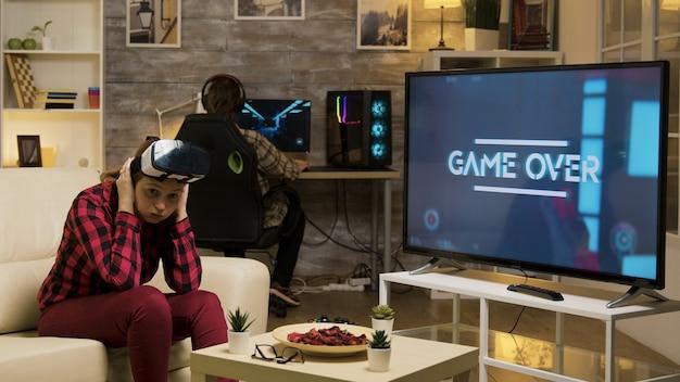 Женщина испытывает виртуальную реальность, играя в видеоигры с помощью гарнитуры vr. игра окончена для женщины-геймера.