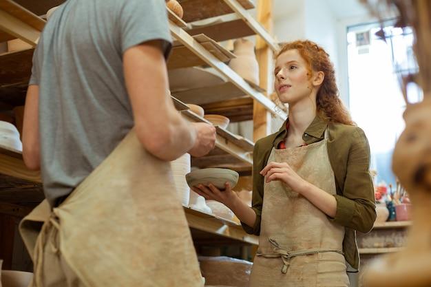 アイデアを説明する女性。塗られた粘土板を持って同僚と話し合う気持ちの良い長髪の女性