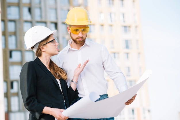 Woman explaining man details of construction plan
