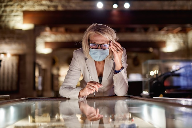Woman exploring medieval expositions in an antivirus mask at museum