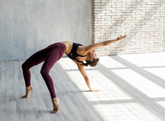 Woman extending her arm in a bridge pose