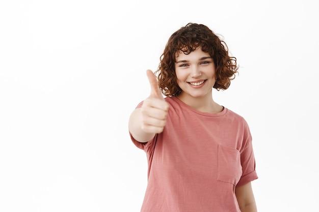 여자는 엄지손가락으로 손을 뻗어 좋은 것을 칭찬하고, 큰 노력을 칭찬하고, 예라고 말하고 승인하고, 흰색 위에 서 있습니다.